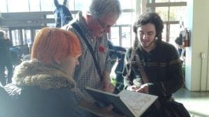Kent Burles, MtM Illustration Coordinator, looking over MtM student's sketches at Royal Winter Fait